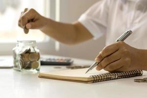ideia para economizar dinheiro. a mão de uma mulher segurando uma caneta para anotar as despesas da casa. foto