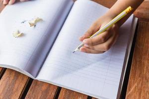 alunos escrevendo na mesa foto
