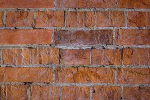 parede de tijolo vermelho com costuras claras e superfície irregular foto