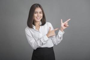 mulher de negócios em camisa branca em fundo cinza foto