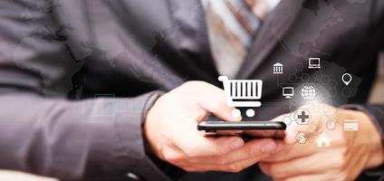 empresário usando smartphone com ícone de carrinho de compras foto