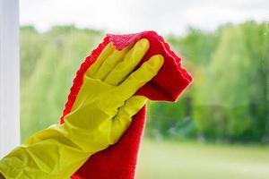 lavagem de janelas e limpeza doméstica. empregada em luvas lava e limpa vidros sujos. foto