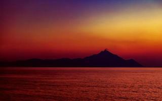 Athos da montanha sagrada ao pôr do sol. vista da praia de platânia, próximo a sarti, sithonia, península halkidiki, grécia. foto
