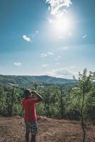 um homem usa seu binóculo e olha para as árvores e a colina da montanha. um homem de camiseta vermelha olha uma bela paisagem com binóculos. foto