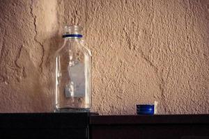 Frasco de vidro pequeno vazio com tampa de metal azul na prateleira preta com fundo de concreto foto