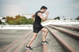 Esportista bonito correndo na cidade ao ar livre foto