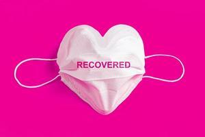 máscara cirúrgica em forma de coração sobre fundo colorido foto
