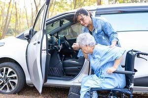 ajudar e apoiar o paciente asiático sênior ou idosa senhora sentada na cadeira de rodas, preparar-se para chegar ao carro dela, conceito médico forte e saudável. foto