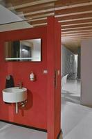 parede vermelha atrás da qual há um lavatório redondo montado na parede e o espelho o chão é feito de concreto e o teto é feito de madeira foto
