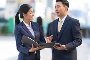 empresário maduro usando um tablet digital para discutir informações com a mulher de negócios foto