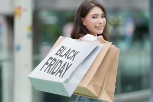 conceito de sexta-feira negra, mulher segurando muitas sacolas de compras e sorrindo na loja durante o processo de compra foto