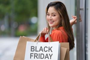 retrato ao ar livre de uma mulher feliz segurando sacolas de compras e um rosto sorridente no shopping foto