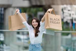 conceito de sexta-feira negra, mulher segurando muitas sacolas de compras e sorrindo foto