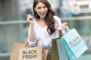 conceito de sexta-feira negra, mulher segurando muitas sacolas de compras com cartão de crédito e sorrindo foto