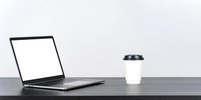 tela branca em branco do laptop na mesa com xícara de café de papel foto