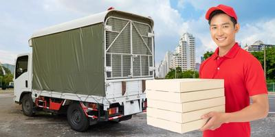 empregado entregador com máscara facial de uniforme de camiseta vermelha segurando uma caixa de papelão vazia foto