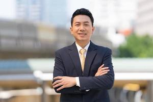 retrato de empresário de sucesso em pé com os braços cruzados em frente a um escritório moderno foto