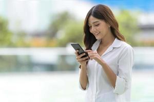 retrato ao ar livre de uma jovem feliz usando um telefone foto