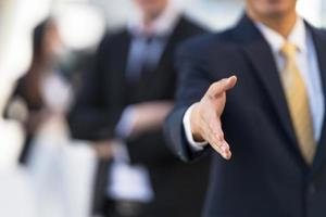 empresário com a mão aberta pronta para um aperto de mão para selar um acordo foto