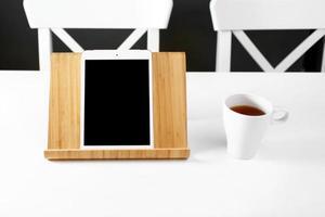 tablet digital de maquete no suporte de madeira. tablet em um suporte de madeira. caneca branca com chá. local de trabalho de escritório foto