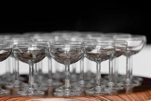 muitos elegantes copos vazios de vinho ou champanhe na mesa de madeira no dia do casamento. conjunto de copos vazios em branco exibidos em linhas. preparação para o feriado foto