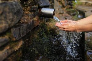 mulher recolhe água pura na palma da mão da fonte na parede, segura e bebe. mão feminina pegando água de nascente da pedra na floresta foto