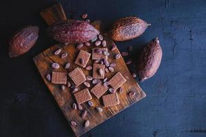 grãos de chocolate e cacau com cacau em um fundo preto foto