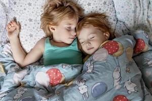duas irmãzinhas irmãs dormindo em um abraço na cama sob o mesmo cobertor foto