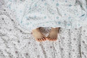 close-up dos pés da menina criança na cama, debaixo do cobertor. tons de azul claro e bege. foto