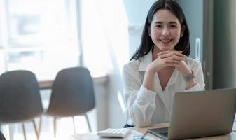 linda jovem asiática trabalhando em um espaço de escritório com um laptop. foto