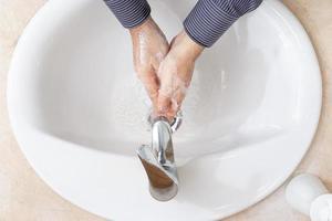 homem lavando as mãos com água e sabão no banheiro conceito de prevenção de coronavírus foto