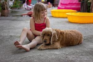 menina sentada no quintal, acariciando seu cachorro foto