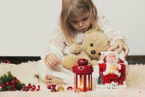 linda garotinha loira sentada no chão, brincando com seu ursinho de pelúcia e o pequeno brinquedo de natal do papai noel foto