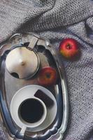 xícara de café, pote moka na bandeja de prata e maçãs no cobertor cinza de malha, vista de cima, fundo aconchegante de inverno foto