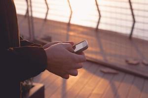 mãos de um homem segurando um smartphone e enviando mensagens de texto, enquanto está do lado de fora foto