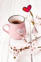café em caneca rosa, flores e coração como decoração, sobre fundo branco de madeira foto