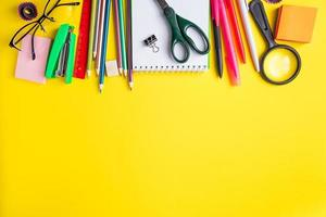 conjunto de material escolar em fundo amarelo. lugar para texto. foto