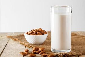 superalimento - um copo de leite de amêndoa para uma dieta saudável. tendência de comida, foto vertical. lugar para o seu texto.