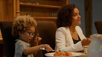 mãe e filho comendo macarrão no jantar foto