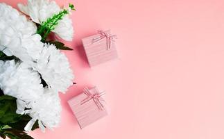 duas caixas de presente rosa com buquê de flores brancas. foto