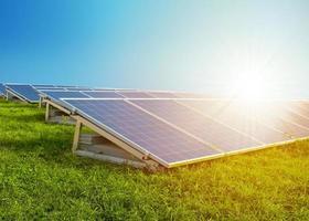 painéis solares na grama verde com sol. céu azul ao fundo. foto