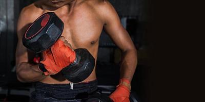 close up de um homem bonito poder esporte atlético com halteres, poderoso homem musculoso levantando peso, boxe tailandês foto