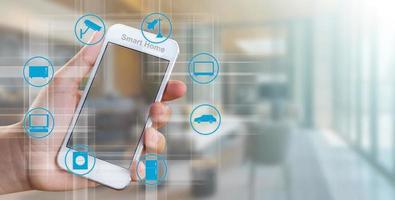 mão de uma mulher segurando um telefone celular, conceito de controlador de casa inteligente foto