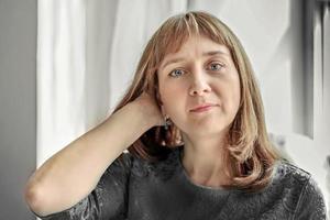retrato de uma jovem junto à janela em cores neutras foto