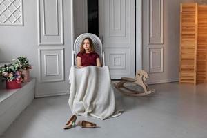 jovem, adolescente, senta-se em seu quarto em uma cadeira de balanço, coberta com um cobertor. descanse depois de uma festa foto