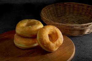 anel donuts coberto de glacê em um prato de madeira foto