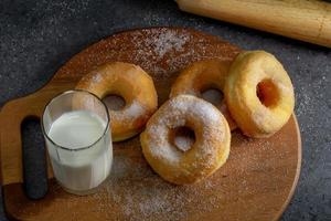 donuts com açúcar em uma placa de madeira sobre um fundo escuro de mesa foto