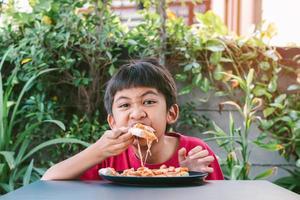 menino bonito asiático de camisa vermelha felizmente sentado comendo pizza. foto