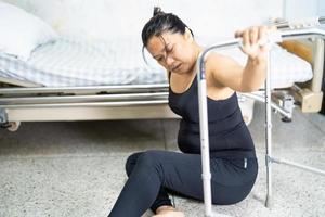 Mulher asiática de meia-idade paciente caindo na sala de estar por causa de superfícies escorregadias foto