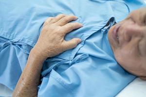 O paciente asiático sênior ou idosa idosa sente dor no peito e no coração na cama, na enfermaria de hospital de enfermagem, conceito médico forte e saudável. foto